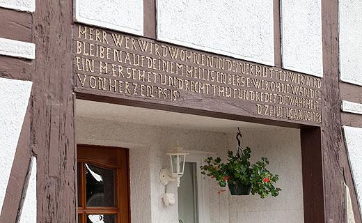 """Auf dem alten Torbogen des Fachwerkhauses von den Asses steht: Herr, wer wird wohnen in Deiner Hütten? Wer wird bleiben auf deinem Heiligen Berge?"""" wird im ersten Vers des Psalm 15 gefragt. Die Antwort steht gleich mit auf dem Torbogen: """"Wer ohne Wandel einhergeht und recht tut und redet die Wahrheit von Herzen."""" Foto: NRW.BANK"""