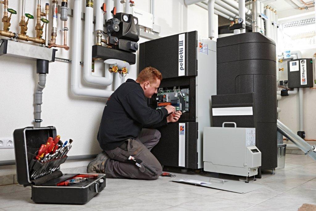 EIn Mitarbeiter von Schäuble Regenerative Energiesysteme installiert die Pelletsheizung im Keller der Gerspachers. Foto: Foto & Design Gröber GmbH & Co. KG