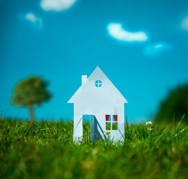 Haus aus Papier auf grüner Wiese