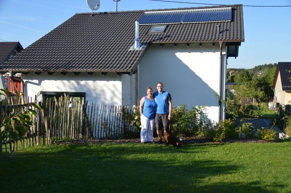 Daniel Jansen, seine Frau Nicole und Hund Bolle vor ihrem Passivhaus mit den Solarthermie-Kollektoren auf dem Dach. Foto: Daniel Jansen