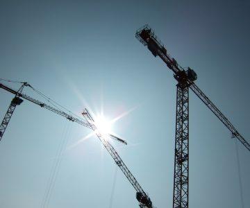 Baukräne vor blauem Himmel mit Sonne