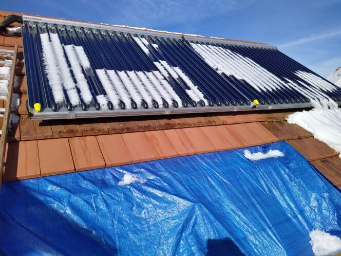 Dach mit Solarthermie-Anlage unter Schneeschmelze